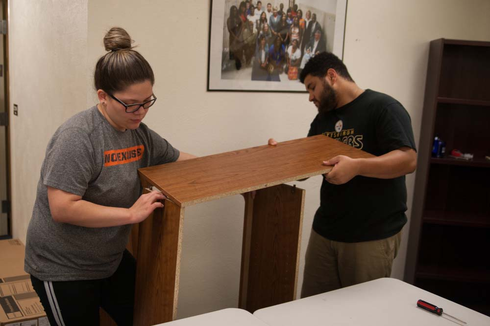 "Volunteers assemble bookcases for Fort Worth ISD ""Reading with Barbers"" Pilot Program"